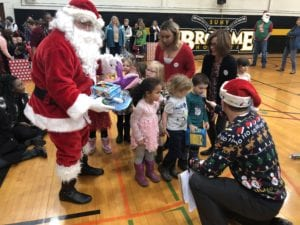 Children from BC Center donate new toys to Santa during the 2018 Giving of the Toys